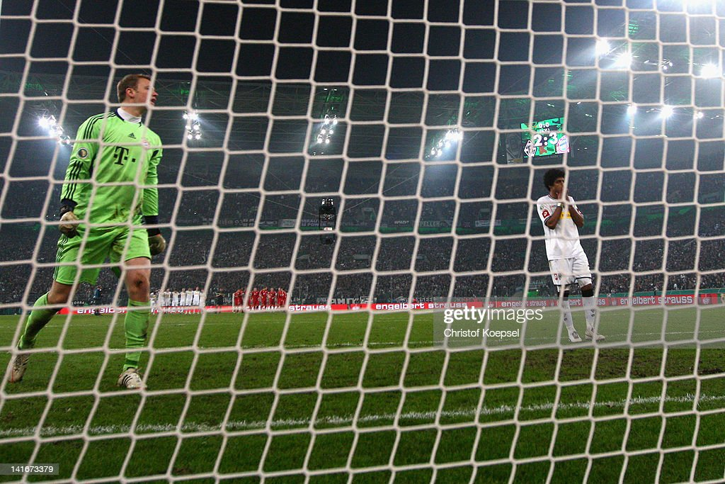 Dante of Moenchengladbach looks dejected after missing a penalty against Manuel Neuer (L) of Bayern during the penalty shoot-out during the DFB Cup semi final match between Borussia Moenchengladbach and FC Bayern Muenchen at Borussia Park Stadium on March 21, 2012 in Moenchengladbach, Germany. Bayern won 4-2 against Moenchengladbach after pelanty-shoot out.