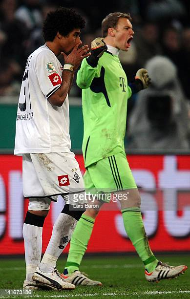 Dante of Moenchengladbach looks dejected next to goalkeeper Manuel Neuer of Muenchen after missing a penalty during the DFB Cup semi final match...