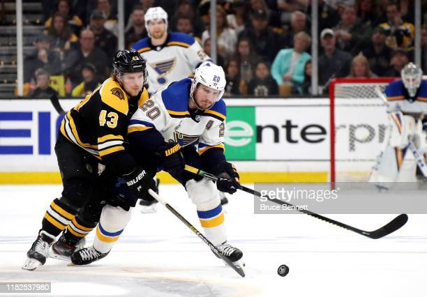 Danton Heinen of the Boston Bruins and Alexander Steen of the St Louis Blues battle for the puck during the third period in Game Two of the 2019 NHL...