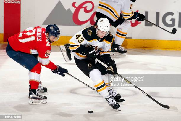Danton Heinen of the Boston Bruins skates with the puck against Vincent Trocheck of the Florida Panthers at the BBT Center on March 23 2019 in...