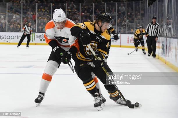 Danton Heinen of the Boston Bruins skates with the puck against Brandon Carlo of the Philadelphia Flyers at the TD Garden on November 10, 2019 in...