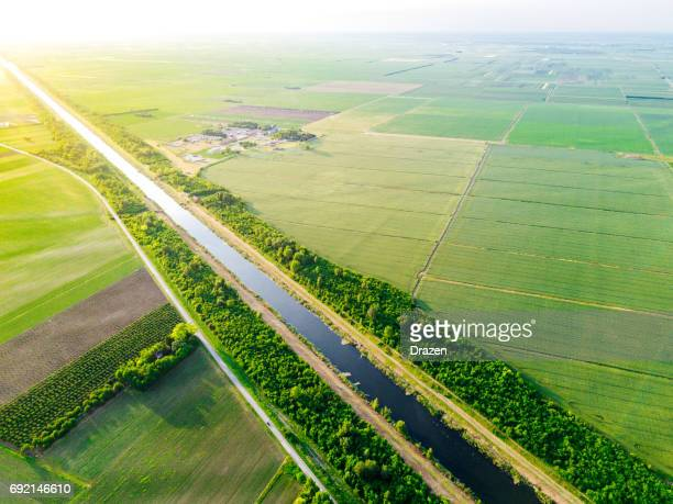 Danube canal stretches between agricultural plots and farms