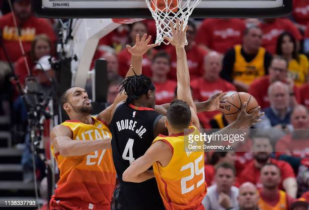 Danuel House Jr #4 of the Houston Rockets passes between Rudy Gobert and Raul Neto of the Utah Jazz in the first half of Game Three during the first...