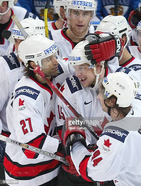 Dany Heatley is congratulated by teammates Scott Niedermayer and Ryan Smyth for Healey's winning overtime goal against Finland in the teams' quarter...