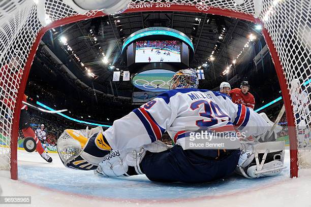 Dany Heatley of Canada scores a goal in the second period against goalie Ryan Miller of the United States during the ice hockey men's preliminary...