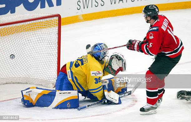 Dany Heatley of Canada scores his team's second goal against goalie Henrik Lundqvist of Sweden in the teams' match at the International Ice Hockey...