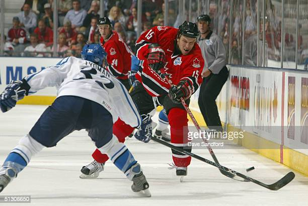 Dany Heatley of Team Canada dumps the puck past Toni Lyndman of Team Finland during the third period of the 2004 World Cup of Hockey Championship...