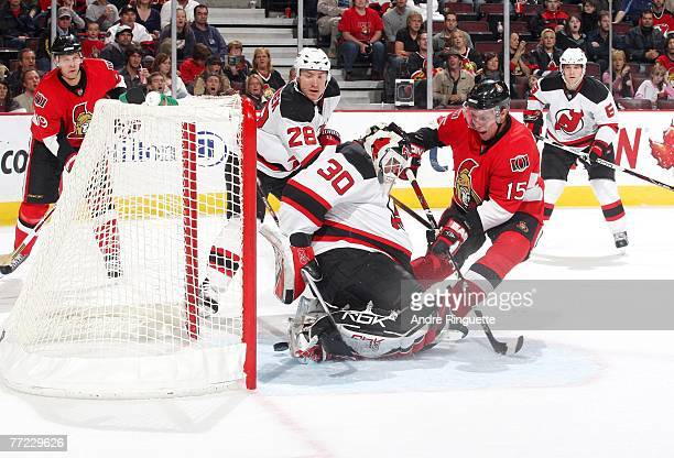 Dany Heatley of the Ottawa Senators knocks the puck past goaltender Martin Brodeur of the New Jersey Devils for the Senators' second goal of the...
