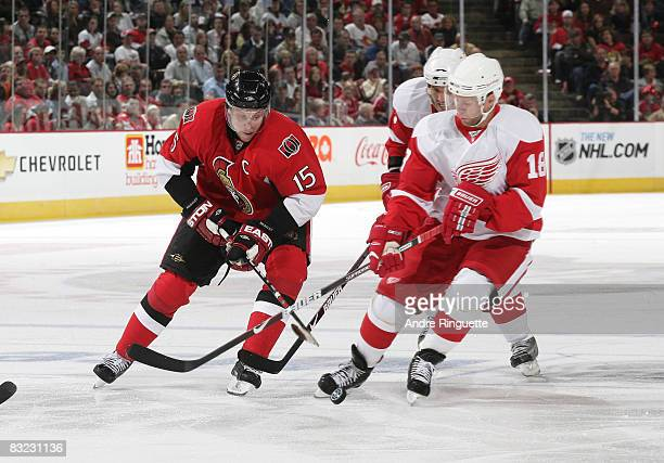 Dany Heatley of the Ottawa Senators stickhandles the puck into the offensive zone against pressure from Kirk Maltby of the Detroit Red Wings at...