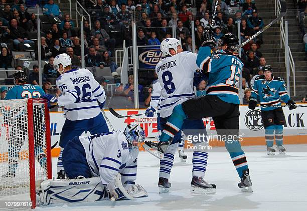 Dany Heatley of the San Jose Sharks battles with Mike Komisarek of the Toronto Maple Leafs in front of Carl Gunnarsson and James Reimer during an NHL...