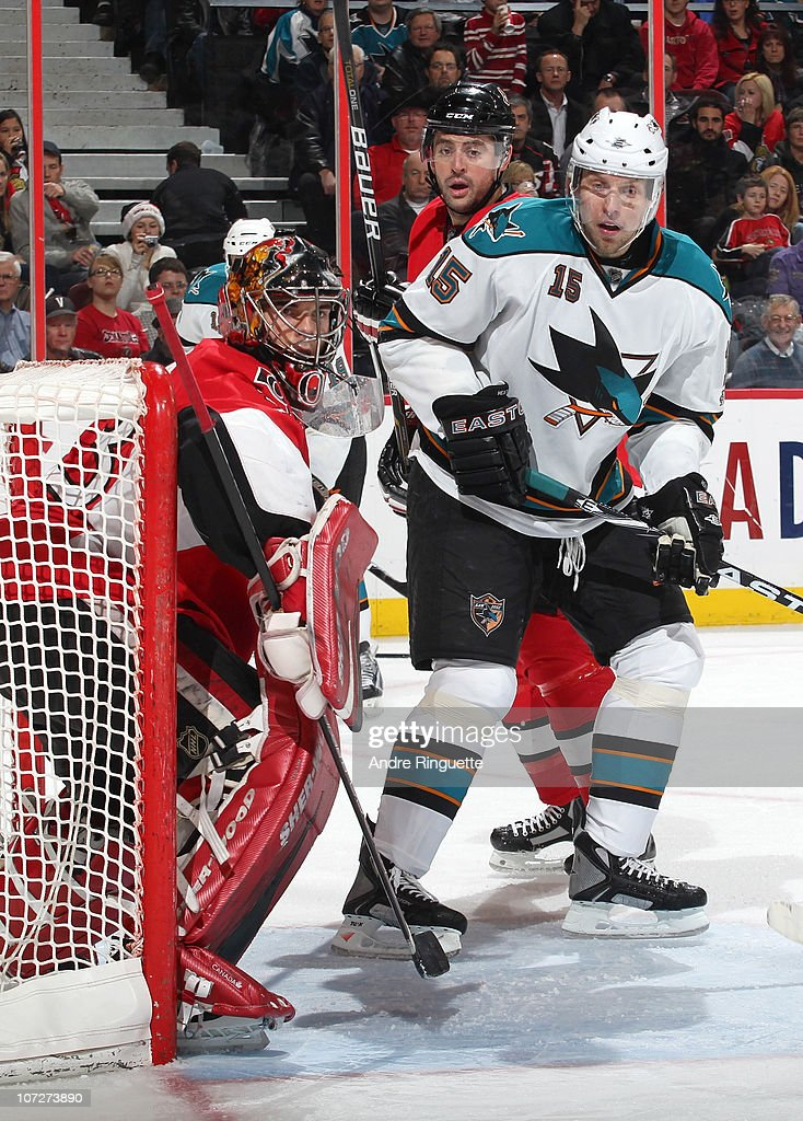 Dany Heatley #15 of the San Jose Sharks skates to the front of the net against Pascal Leclaire #33 and Chris Phillips #4 of the Ottawa Senators at Scotiabank Place on December 2, 2010 in Ottawa, Ontario, Canada.