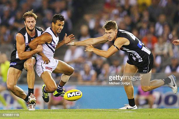 Danyle Pearce of the Dockers is tackled by Alan Toovey and Tom Langdon of the Magpies during the round one AFL match between the Collingwood Magpies...