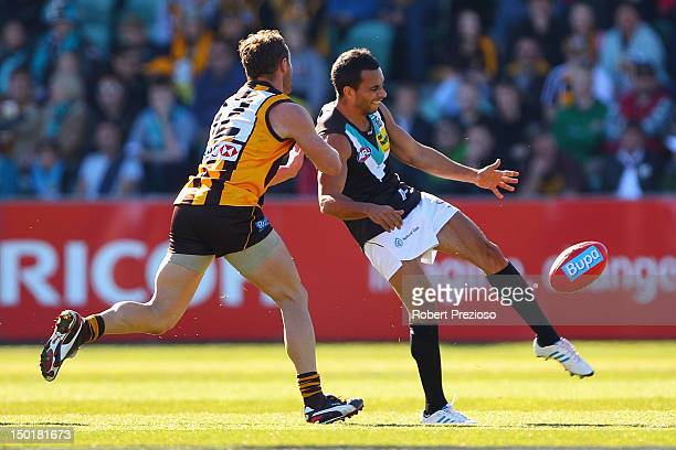 Danyle Pearce of the Power kicks under pressure from Brad Sewell of the Hawks during the round 20 AFL match between the Hawthorn Hawks and the Port...