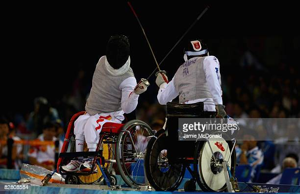 Daoliand Hu of China fences with Laurent Francois Laurent of France in the Individual Foil Category B Final in the Wheelchair Fencing Competition at...