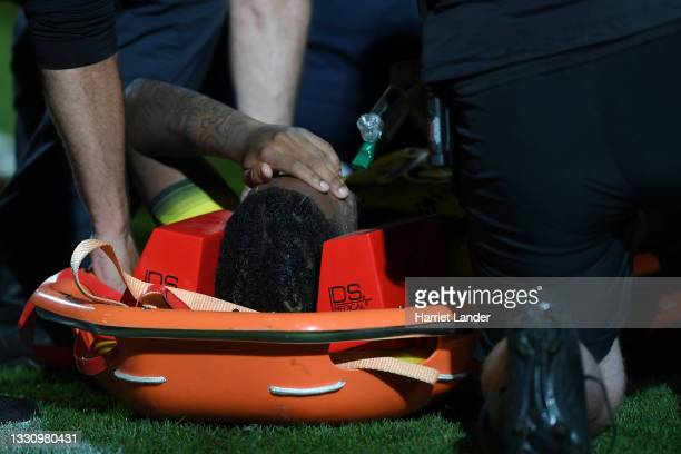 Dapo Mebude of Watford looks dejected as he lies on a stretcher after getting injured during the Pre-Season Friendly match between Stevenage and...