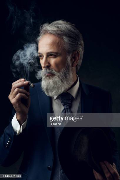 dapper gentleman having fashion photoshooting in studio - cigar stock pictures, royalty-free photos & images