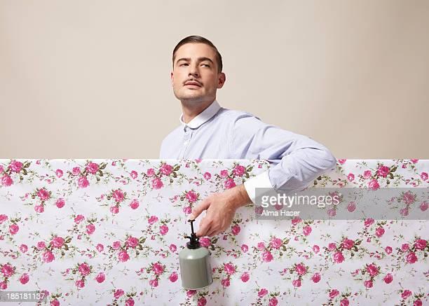 A dapper man spraying flowers on material