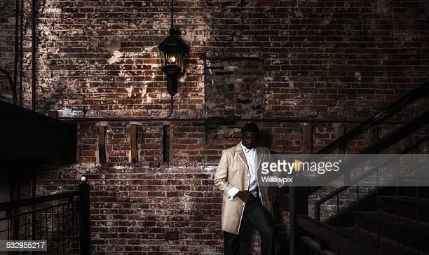 Dapper Young Black Man Wearing Hot Tuxedo in Dark Building