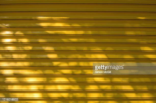dappled light on a metal roller shutter painted yellow - roller shutter stock pictures, royalty-free photos & images