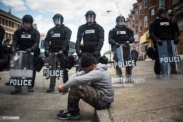 Daquan Green, age 17, sits on the curb while riot police stand guard near the CVS pharmacy that was set on fire yesterday during rioting after the...