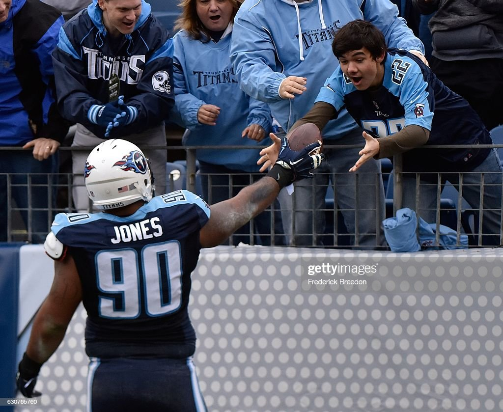 DaQuan Jones #90 of the Tennessee Titans hands a game ball to a young fan after scoring a touchdown against the Houston Texans during the first half at Nissan Stadium on January 1, 2017 in Nashville, Tennessee.