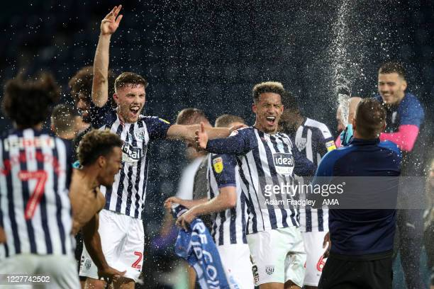 Dara O'Shea and Callum Robinson of West Bromwich Albion spray champagne as he celebrates promotion to the Premier League on the pitch at the end of...