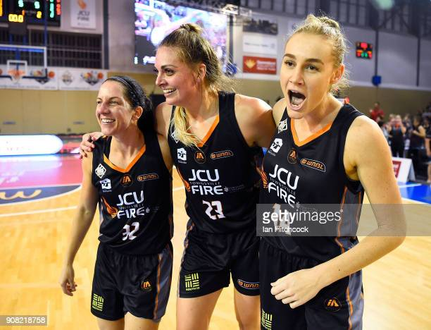 Darcee Garbin Cayla George and Cayla George of the Fire celebrate after winning game three of the WNBL Grand Final series between the Townsville Fire...