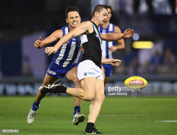 Darcy Byrne-Jones of the Power kicks whilst being tackled by Ben Jacobs of the Kangaroos during the round six AFL match between the North Melbourne...
