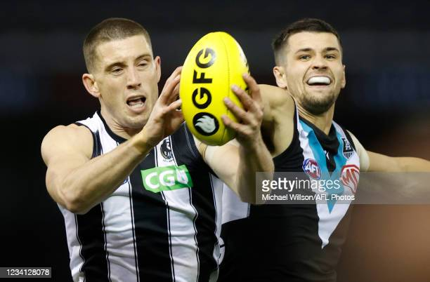 Darcy Cameron of the Magpies and Ryan Burton of the Power in action during the 2021 AFL Round 19 match between the Port Adelaide Power and the...