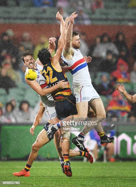 Darcy Fogarty of the Adelaide Crows crashes through Zaine Cody and Jordan Roughead of the Bulldogs during the round nine AFL match between the...