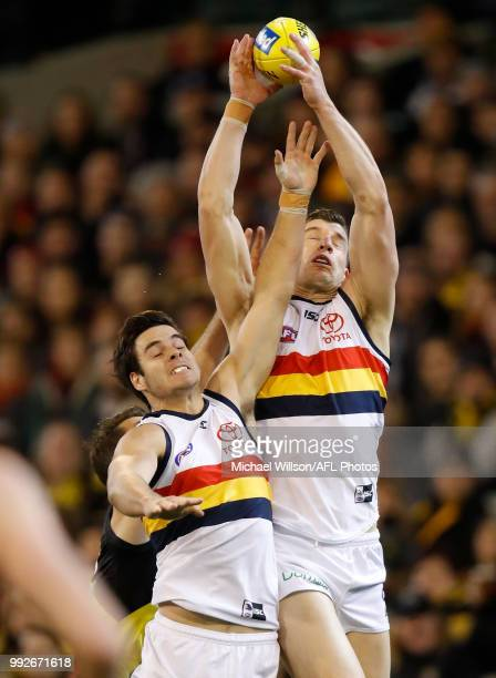 Darcy Fogarty of the Crows and teammate Josh Jenkins attempt to catch the ball during the 2018 AFL round 16 match between the Richmond Tigers and the...
