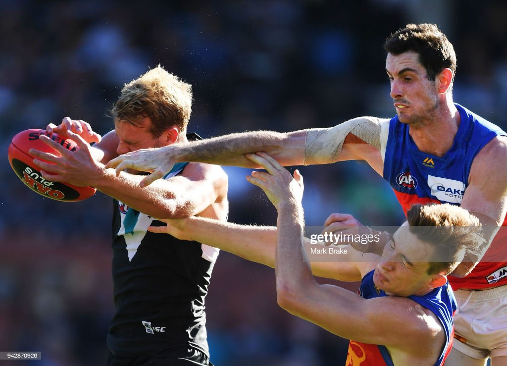 Darcy Gardiner and Harris Andrews of the Lions attempt to spoil Tom Jonas of Port Adelaide during the round three AFL match between the Port Adelaide Power and the Brisbane Lions at Adelaide Oval on April 7, 2018 in Adelaide, Australia.
