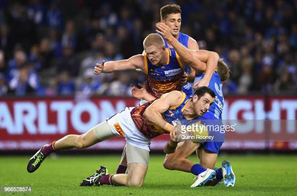 Darcy Gardiner of the Lions handballs during the round 11 AFL match between the North Melbourne Kangaroos and the Brisbane Lions at Etihad Stadium on...