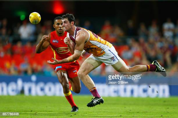 Darcy Gardiner of the Lions handballs during the round one AFL match between the Gold Coast Suns and the Brisbane Lions at Metricon Stadium on March...