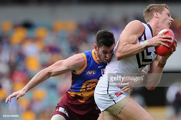 Darcy Gardiner of the Lions tackles Matt Taberner of the Dockers during the round 22 AFL match between the Brisbane Lions and the Fremantle Dockers...