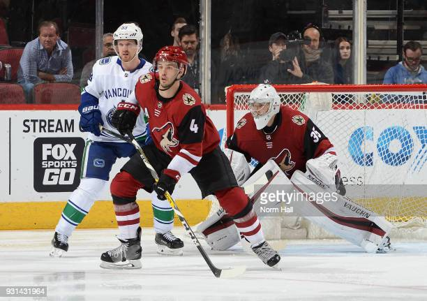 Darcy Kuemper and Niklas Hjalmarsson of the Arizona Coyotes and Henrik Sedin of the Vancouver Canucks all look for the puck from in front of the...