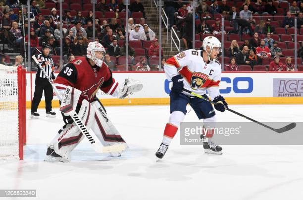 Darcy Kuemper of the Arizona Coyotes gets ready to make a save while being screened by Aleksander Barkov of the Florida Panthers at Gila River Arena...