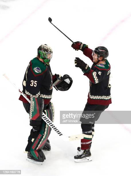 Darcy Kuemper of the Arizona Coyotes is congratulated by teammate Jakob Chychrun after the 41 win over the Nashville Predators after Game Three of...