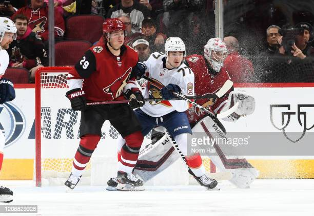 Darcy Kuemper of the Arizona Coyotes looks to make a save as teammate Barrett Hayton battles for position with Frank Vatrano of the Florida Panthers...
