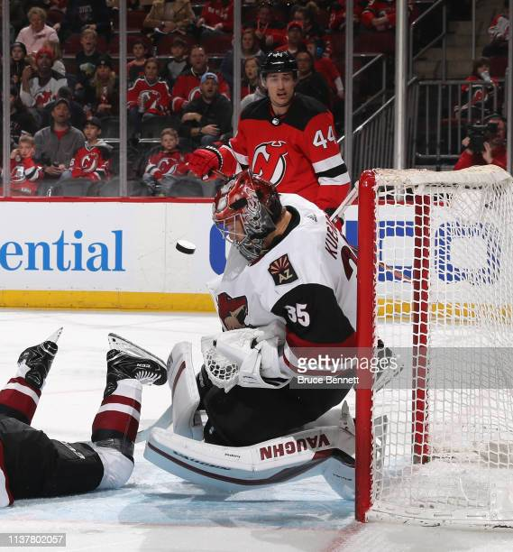 Darcy Kuemper of the Arizona Coyotes makes the second period stop as Miles Wood of the New Jersey Devils looks for the rebound at the Prudential...