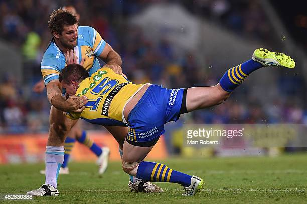 Darcy Lussick of the Eels is tackled by Dave Taylor of the Titans during the round 21 NRL match between the Gold Coast Titans and the Parramatta Eels...