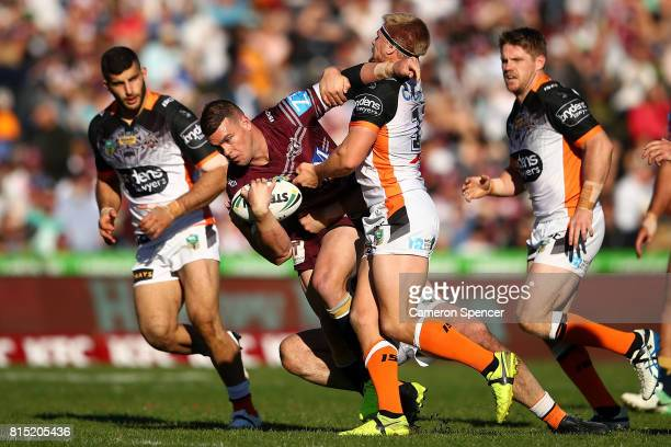 Darcy Lussick of the Sea Eagles is tackled during the round 19 NRL match between the Manly Sea Eagles and the Wests Tigers at Lottoland on July 16...