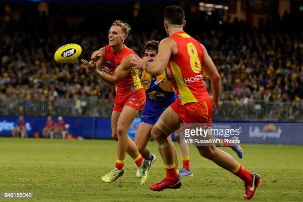 Darcy MacPherson of the Suns handpasses the ball during the round four AFL match between the West Coast Eagles and the Gold Coast Suns at Optus...