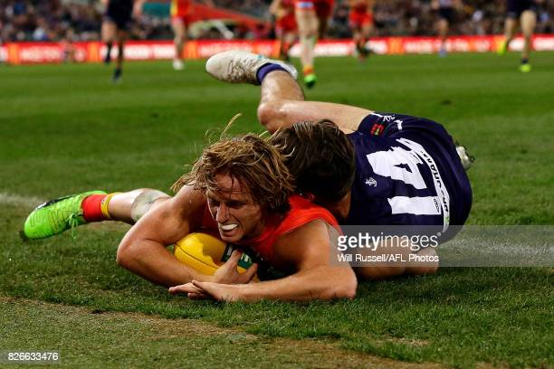 Darcy MacPherson of the Suns is tackled by Lachie Weller of the Dockers during the round 20 AFL match between the Fremantle Dockers and the Gold...