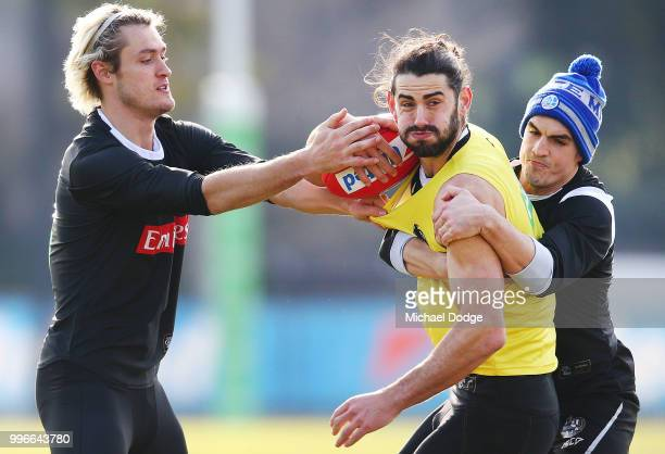 Darcy Moore of the Magpies and Brayden Maynard tackle Brodie Grundy of the Magpies during a Collingwood Magpies AFL press conference at the Holden...