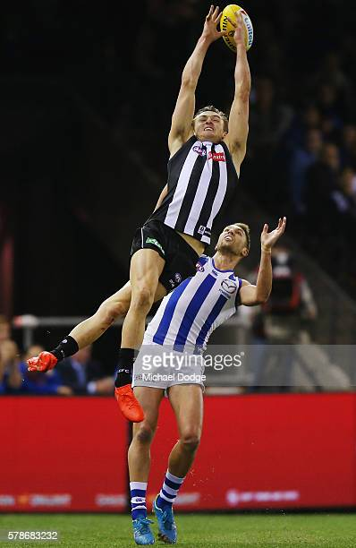 Darcy Moore of the Magpies compete for the ball ahead of Jamie Macmillan of the Kangaroos during the round 18 AFL match between the Collingwood...