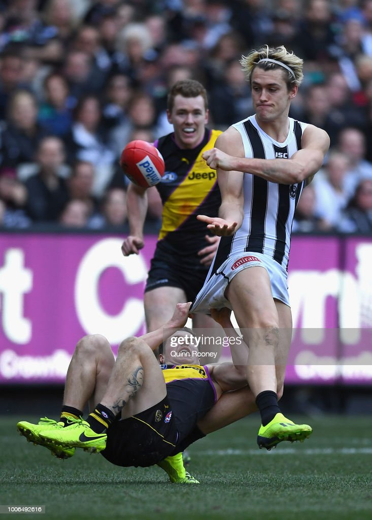 Darcy Moore of the Magpies handballs whilst being tackled by Liam Baker of the Tigers during the round 19 AFL match between the Richmond Tigers and the Collingwood Magpies at Melbourne Cricket Ground on July 28, 2018 in Melbourne, Australia.