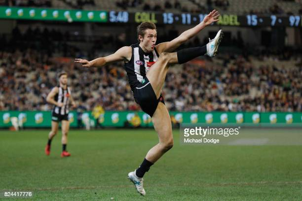 Darcy Moore of the Magpies kicks the ball for a point in the dying stages during the round 19 AFL match between the Collingwood Magpies and the...
