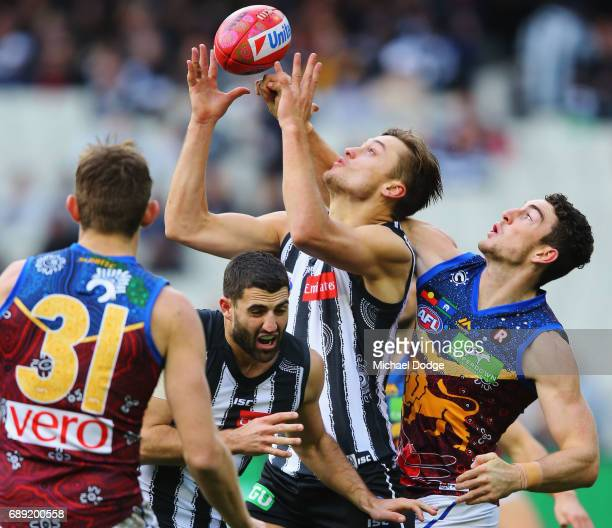 Darcy Moore of the Magpies marks the ball against Darcy Gardiner of the Lions during the round 10 AFL match between the Collingwood Magpies and...