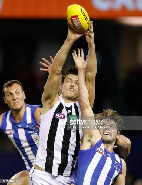 Darcy Moore of the Magpies marks the ball over Braydon Preuss and Luke McDonald of the Kangaroos during the 2017 AFL round 20 match between the North...